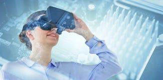 Составное изображение взгляда низкого угла коммерсантки используя шлемофон виртуальной реальности Стоковое фото RF
