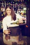 Составное изображение вискиа милого бармена лить в стекле стоковое изображение