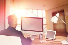 Составное изображение вид сзади бизнесмена работая над компьютером Стоковое Изображение