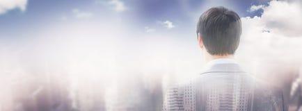 Составное изображение вид сзади бизнесмена смотря через окно строить 3d Стоковое фото RF