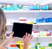 Составное изображение вид сзади женщины используя ПК таблетки Стоковые Фото
