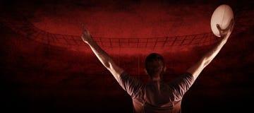 Составное изображение вид сзади игрока рэгби держа шарик с оружиями поднятый Стоковые Изображения RF