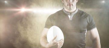 Составное изображение грубого игрока рэгби держа шарик Стоковые Изображения