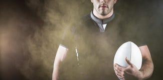 Составное изображение грубого игрока рэгби держа шарик Стоковое фото RF