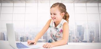 Составное изображение девушки используя компьтер-книжку на таблице Стоковая Фотография