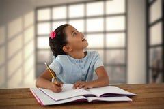 Составное изображение девушки смотря вверх пока пишущ в книге Стоковая Фотография RF