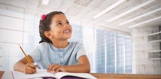 Составное изображение девушки смотря вверх пока сидящ на столе Стоковая Фотография