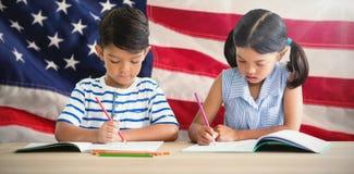 Составное изображение детей писать на книгах на таблице Стоковая Фотография