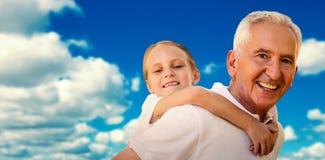 Составное изображение деда держа его внука на его назад Стоковые Изображения