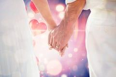 Составное изображение жениха и невеста держа поднимающее вверх рук близкое Стоковые Изображения RF
