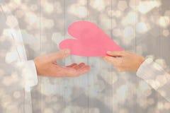 Составное изображение женщины вручая человеку бумажное сердце Стоковые Изображения