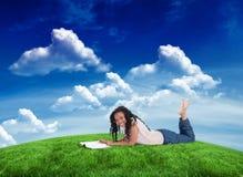 Составное изображение женщины лежа на поле усмехаясь на камере с кассетой перед ей Стоковое фото RF