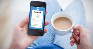 Составное изображение женщины используя ее мобильный телефон и держащ чашку кофе Стоковое Изображение