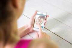 Составное изображение женщины используя ее smartphone Стоковые Изображения