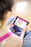 Составное изображение женщины используя таблетку дома Стоковая Фотография