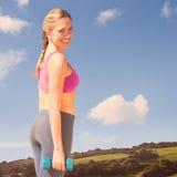 Составное изображение женщины пригонки разрабатывая с гантелями на пляже усмехаясь на камере Стоковая Фотография RF