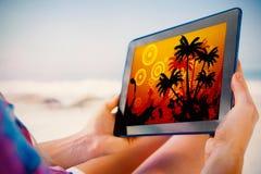 Составное изображение женщины сидя на пляже в шезлонге используя ПК таблетки Стоковые Изображения RF
