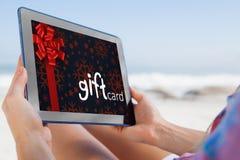 Составное изображение женщины сидя на пляже в шезлонге используя ПК таблетки Стоковое Изображение RF