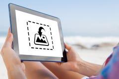 Составное изображение женщины сидя на пляже в шезлонге используя ПК таблетки Стоковые Фотографии RF