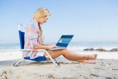 Составное изображение женщины сидя на пляже используя ее компьтер-книжку Стоковые Фотографии RF