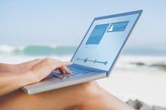 Составное изображение женщины сидя на пляже используя ее компьтер-книжку Стоковая Фотография RF
