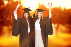 Составное изображение 2 женщин празднуя их градацию Стоковое Фото