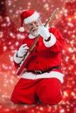 Составное изображение жизнерадостного Санта Клауса вставать и играя гитару Стоковое Изображение