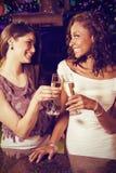 Составное изображение жизнерадостных молодых женщин провозглашать каннелюры шампанского на счетчике бара Стоковые Фото