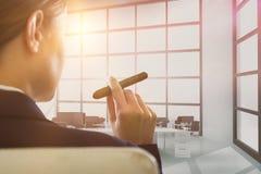 Составное изображение коммерсантки держа сигару Стоковые Изображения