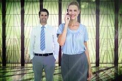 Составное изображение коммерсантки имея телефонный звонок пока ее представлять коллеги Стоковые Изображения