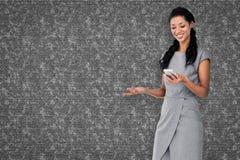 Составное изображение коммерсантки используя smartphone Стоковое Фото