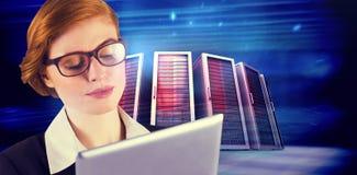 Составное изображение коммерсантки redhead используя ее ПК таблетки Стоковая Фотография