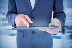 Составное изображение конца вверх по взгляду бизнесмена используя планшет Стоковое Фото