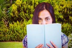 Составное изображение конца вверх по портрету женщины пряча за книгой Стоковые Изображения RF