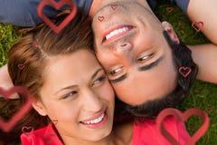 Составное изображение конца вверх по 2 друзьям смотря один другого пока лежа голова к плечу Стоковая Фотография