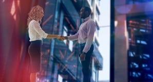 Составное изображение корпоративного человека и женщины делая рукопожатие Стоковые Фотографии RF
