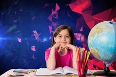 Составное изображение милого зрачка работая на ее столе Стоковое Фото
