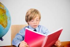 Составное изображение милого чтения зрачка на столе Стоковое фото RF