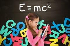Составное изображение милой девушки используя таблетку Стоковая Фотография