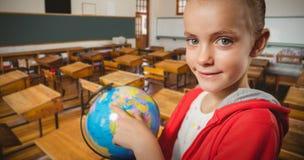 Составное изображение милой девушки указывая на глобус Стоковые Фотографии RF