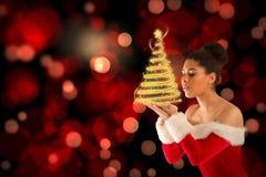 Составное изображение милой девушки santa дуя над ее руками Стоковая Фотография RF