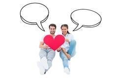 Составное изображение милых пар сидя держащ красное сердце Стоковое Изображение