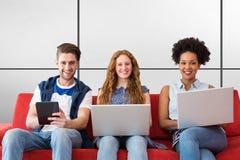 Составное изображение молодых взрослых используя электронные устройства на кресле стоковая фотография