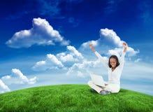 Составное изображение молодой женщины протягивая пока на поле с ее компьтер-книжкой Стоковое Изображение