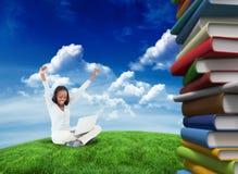 Составное изображение молодой женщины протягивая пока на поле с ее компьтер-книжкой Стоковые Изображения RF