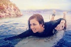 Составное изображение молодой женщины плавая над surfboard Стоковые Фото