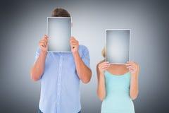 Составное изображение молодых пар держа страницы над их сторонами Стоковые Фотографии RF