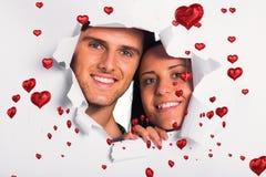 Составное изображение молодых пар смотря через бумажный сулой Стоковые Фотографии RF