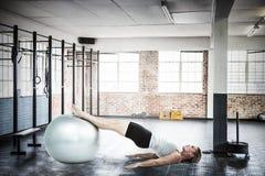 Составное изображение мышечной женщины лежа на поле с ногами Стоковое Изображение RF