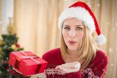 Составное изображение довольно белокурого в моде зимы дуя над руками Стоковые Фотографии RF